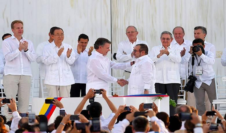 O presidente da Colômbia, Juan Manuel Santos, aperta a mão de Rodrigo Londoño, o Timochenko, líder das FARC, depois da assinatura do acordo final. (Foto: Presidência da Colômbia)